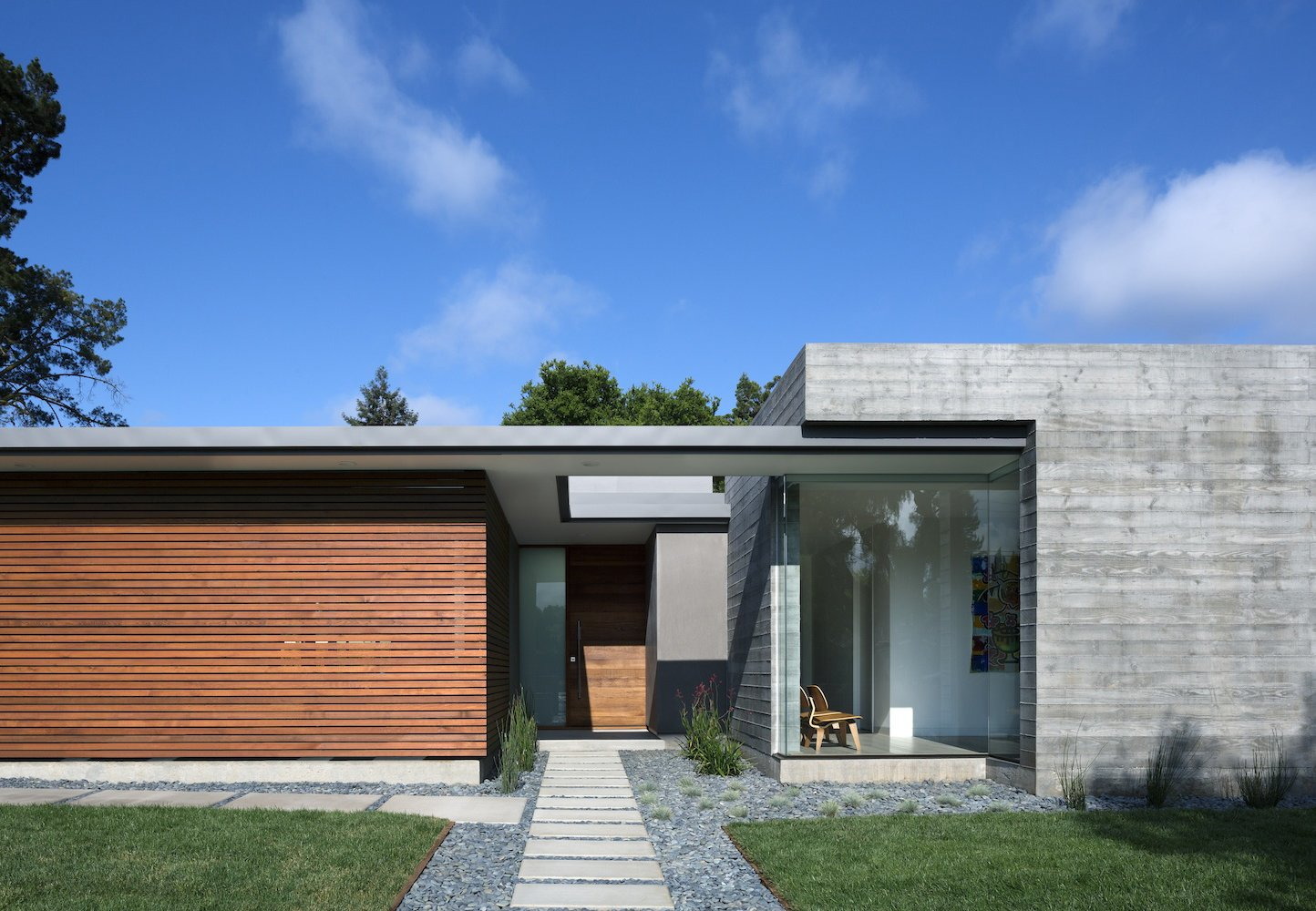 Located in Los Altos, California, Curt Cline's modern house seeks to respect the neighborhood fabric. By keeping the abode low-slung, using a few simple geometries, and the leaving the facade spare, Cline helped the structure blend in with the 1940s and 1950s structures around it. The materials—board-formed concrete and cedar slats—instill a contemporary California aesthetic.  Concrete Obsessed