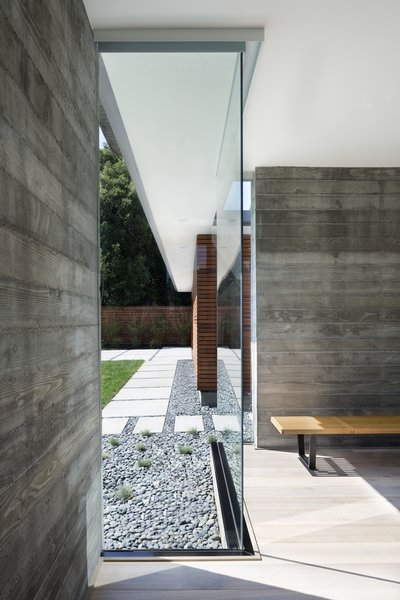Floor-to-ceiling glass walls help the house connect to the landscape and also offer a material contrast to the oak floors and concrete.