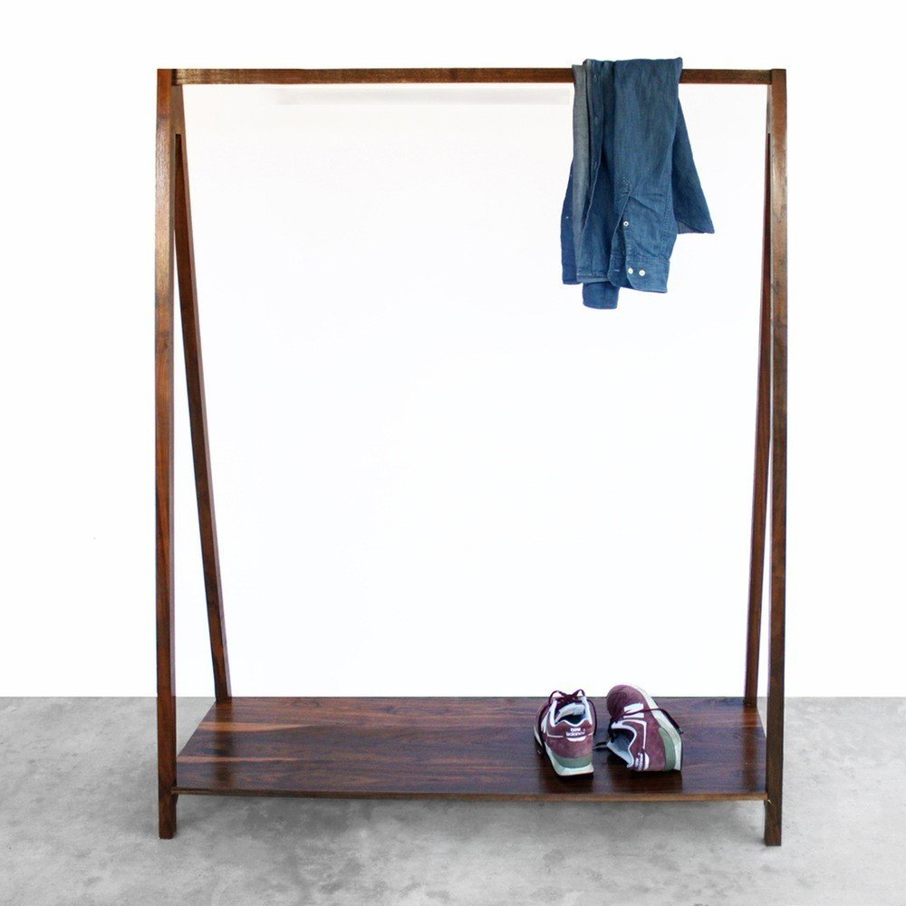 The Walnut Coat Rack takes a simple household accent and elevates it with rich walnut wood. Featuring a trestle shape, the coat rack includes a base on which to rest shoes and boots, and a connecting bar that can be used to hold hangers or drape scarves and jackets. The result is a balanced piece that is geometric and refined.  Shelves