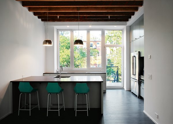 All of the Jenn-Air appliances, including the washer and dryer, are electric, as the owners asked the city to cut the gas line to the house. The kitchen cabinetry is from IKEA and features custom, matte-gray doors and Silestone countertops. The floorboards are reclaimed maple from an old tire factory, sanded and stained gray.