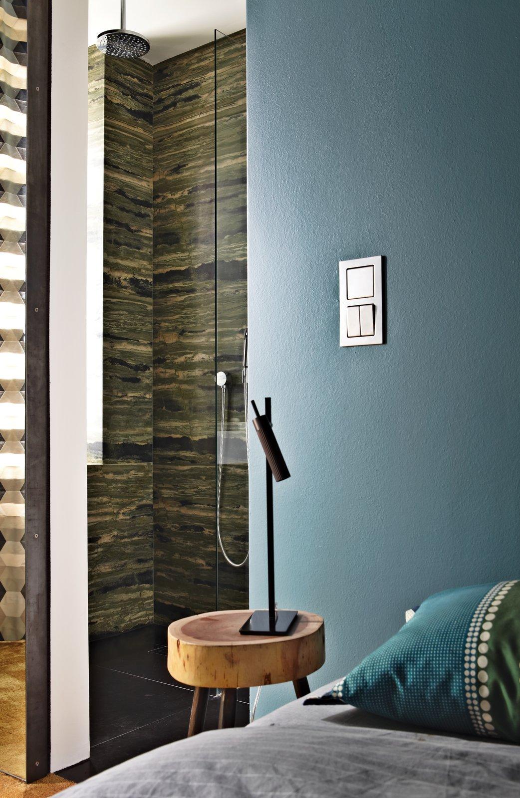 A sliding door divides the verde bamboo granite bathroom from the bedroom.  127+ Inspiring Interior Ideas from Inside Peter Fehrentz's Renovated Flat in Berlin