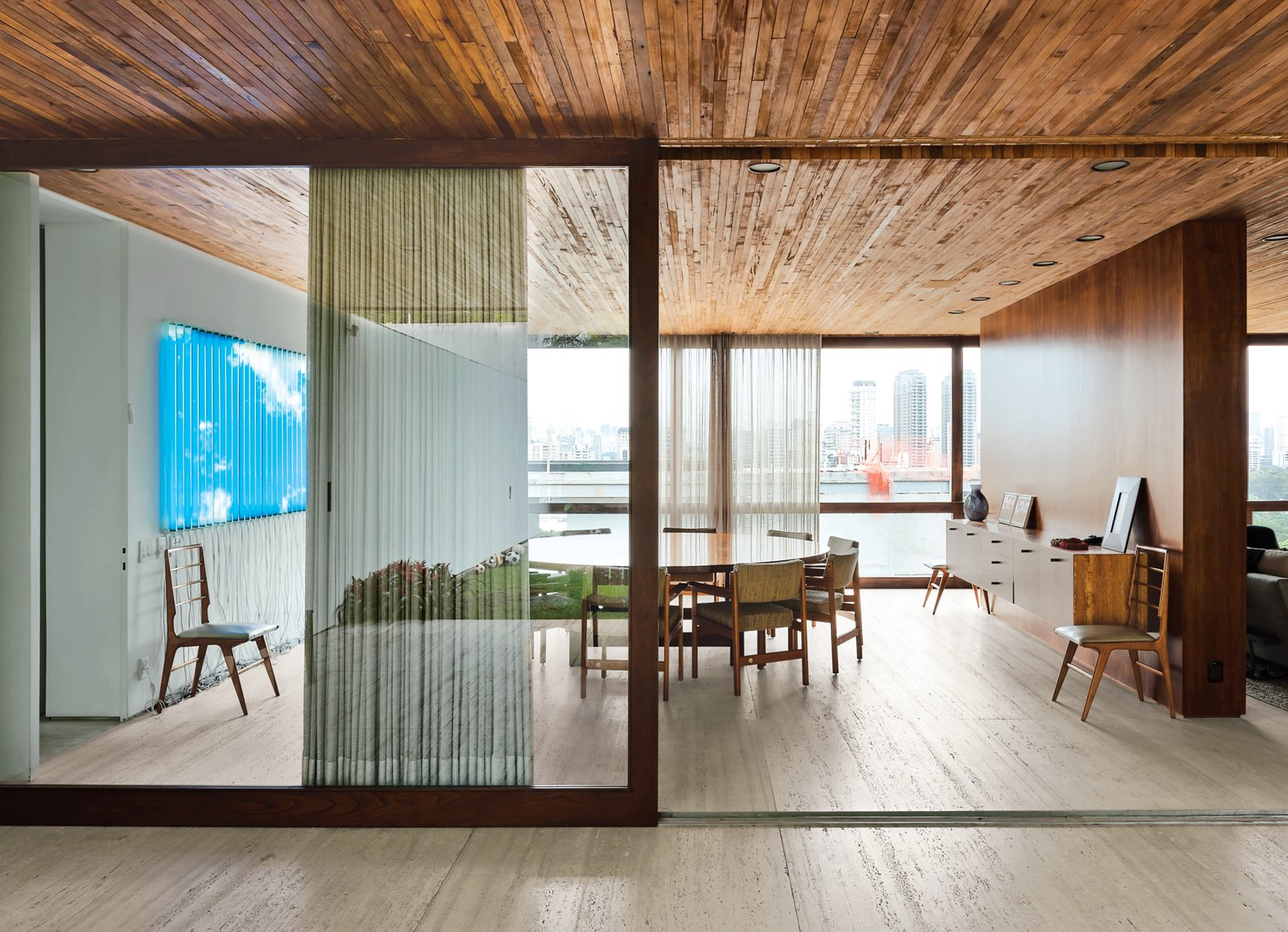 A wooden partition separates the dining room from the living room. The jacaranda table is a vintage find designed by Jorge Zalszupin for L'Atelier. The dining chairs are by the Brazilian designer Sergio Rodrigues and architect Isay Weinfeld designed the sideboard. The fluorescent lamp sculpture on the wall is Luz Natural by Eduardo Coimbra.  Latin America's Best Modern Homes by Kelsey Keith from Blockbuster Movies Can't Compete with These Monumental Views
