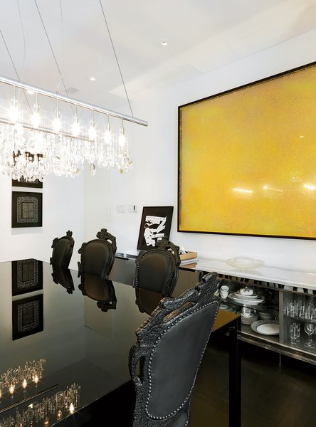 The dining room's high drama is thanks to a Cellula chandelier by Nunzia Carbone and Tiziano Vudafieri, a sleek Colors table by B. Fattorini for MDF Italia, and a massive yellow painting on the wall by Polish artist Pitor Uklański.