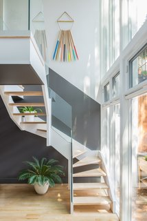 The back staircase abuts a glass facade overlooking the backyard, allowing plenty of light into the kitchen area above. The art hanging on the wall is by artist Julie Thevenot.