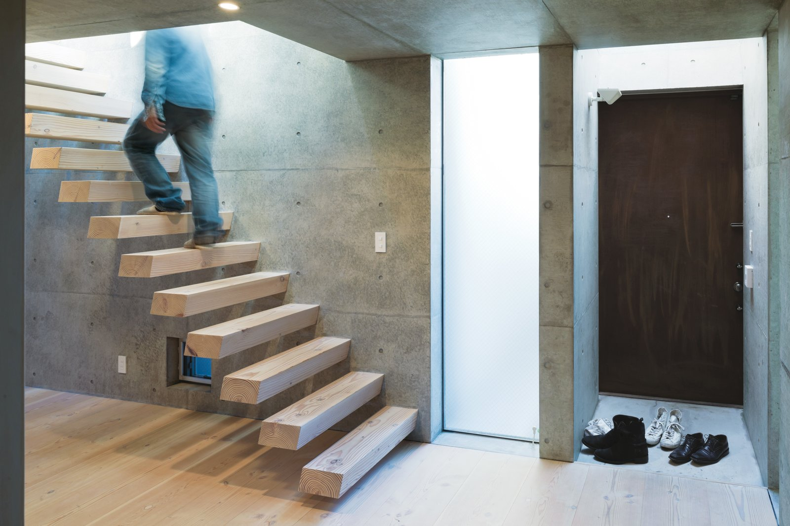 Staircase and Wood Tread Tsutsui continued the Oregon pine from the floor to the steel-reinforced cantilevered staircase, which appears to float above the floor.  Photo 8 of 11 in 11 Ways to Create a Modern Mudroom in Your Home from Open-Plan Concrete Home in Japan