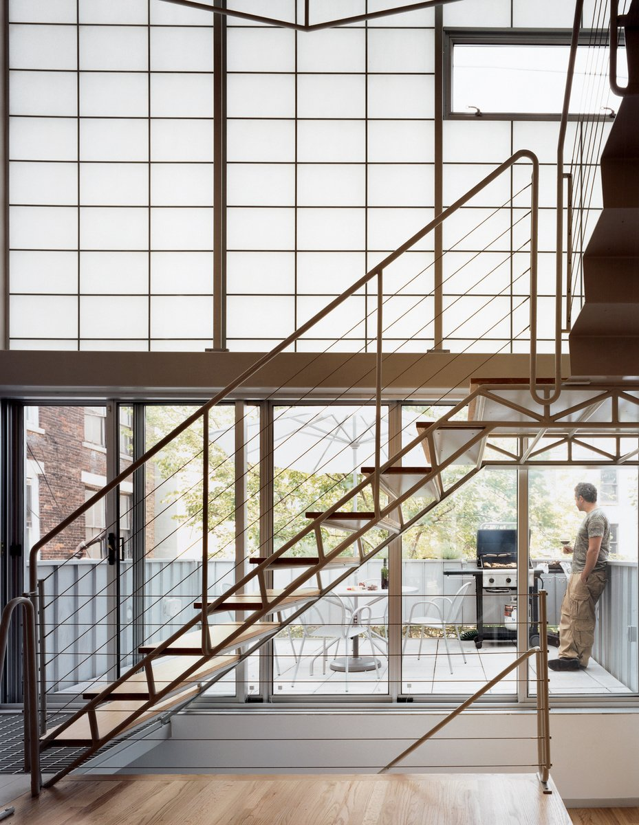 Yvette Leeper-Bueno and Adrian Bueno's home, on West 112th Street in New York, is recognizable by its two-story bay window angled to bring light and views into the dark, narrow structure. Seemingly a single, seamless unit, the stair is composed of two elements—treads and mezzanine—and held in place by two distinct strategies: The stairs are welded to, and cantilever out from, a series of steel tubes concealed in the walls; the mezzanine is attached on one side to a steel beam, and hung at two other points from rods attached to the roof structure. Photo by: Adam Friedberg  190+ Best Modern Staircase Ideas from Staircases We Love