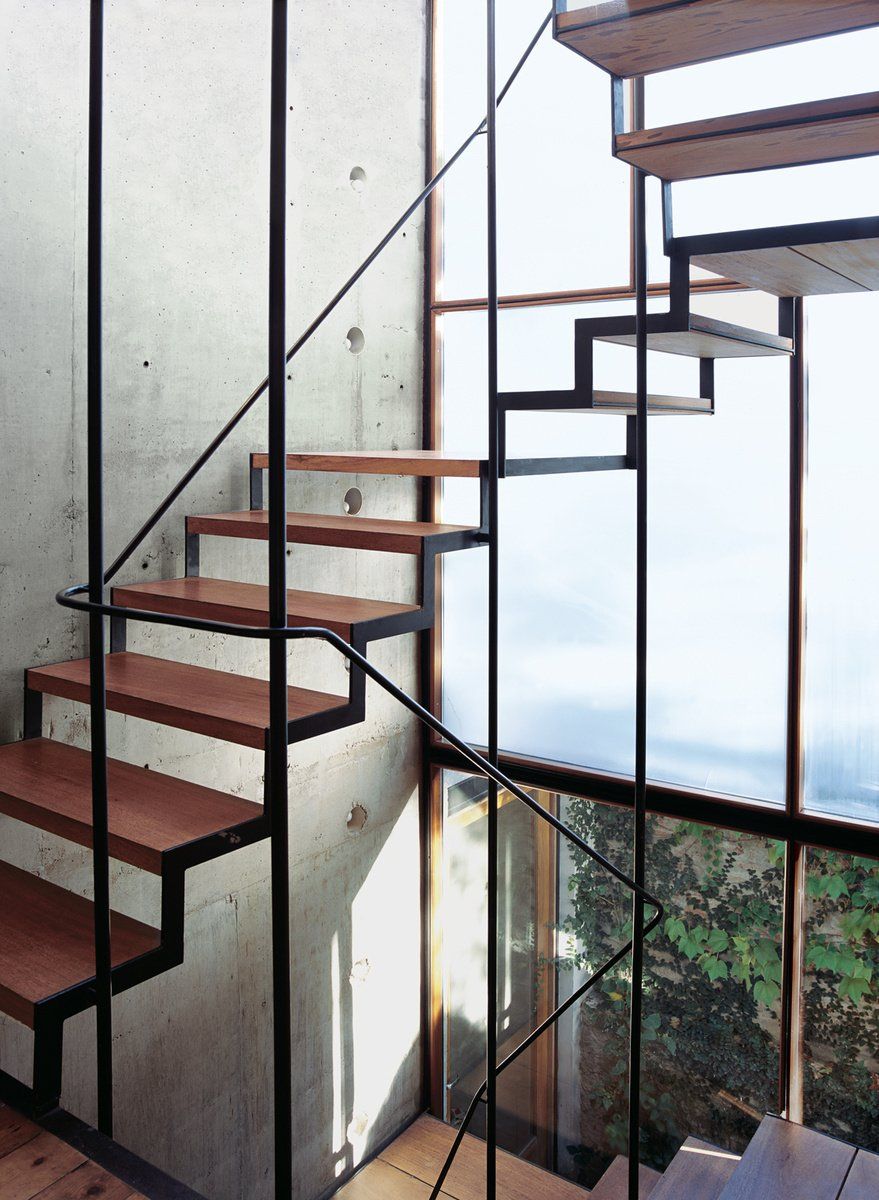 Argentinean materials, a roiling economy, and a pinch of personal tumult served as the recipe for furniture designer Alejandro Sticotti's Buenos Aires oasis. The wood-and-steel open staircase wends its way up three stories, supported by a concrete structural wall embedded with PVC tubes and bare lightbulbs. Photo by: Cristóbal Palma  190+ Best Modern Staircase Ideas from Staircases We Love