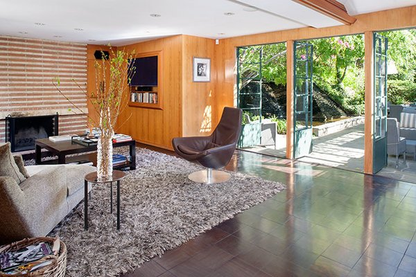 Like many of Wright's Los Angeles designs, the property prioritizes indoor/outdoor connection and rich materials including cypress paneling and Brazilian walnut tile flooring.