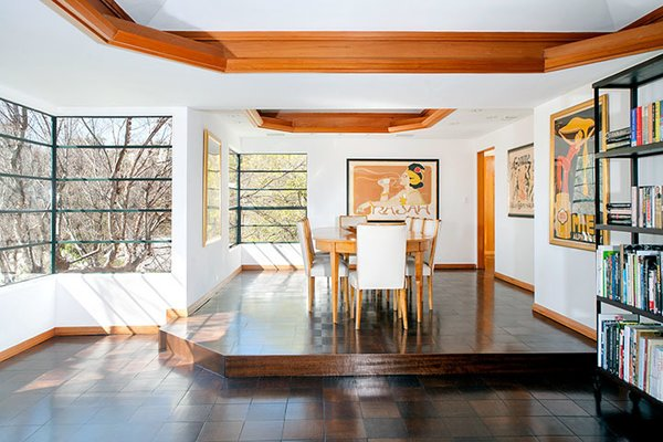 The elevated dining area room looks out onto the half-acre site. In recent years, the house has been restored.