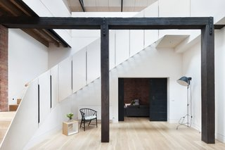 "Minimal interventions by architect Andrew Simpson allowed this former jam warehouse outside of Melbourne, Australia, to be turned into a family residence. ""To draw light and ventilation into what was a poorly oriented and deep footprint, an extensive number of operable skylights were introduced on the north- and south-facing roof pitches, and a large void connecting the floors was strategically positioned to also take advantage of this amenity,"" Simpson says. American oak floorboards and Dulux paint were used throughout the property for continuity."