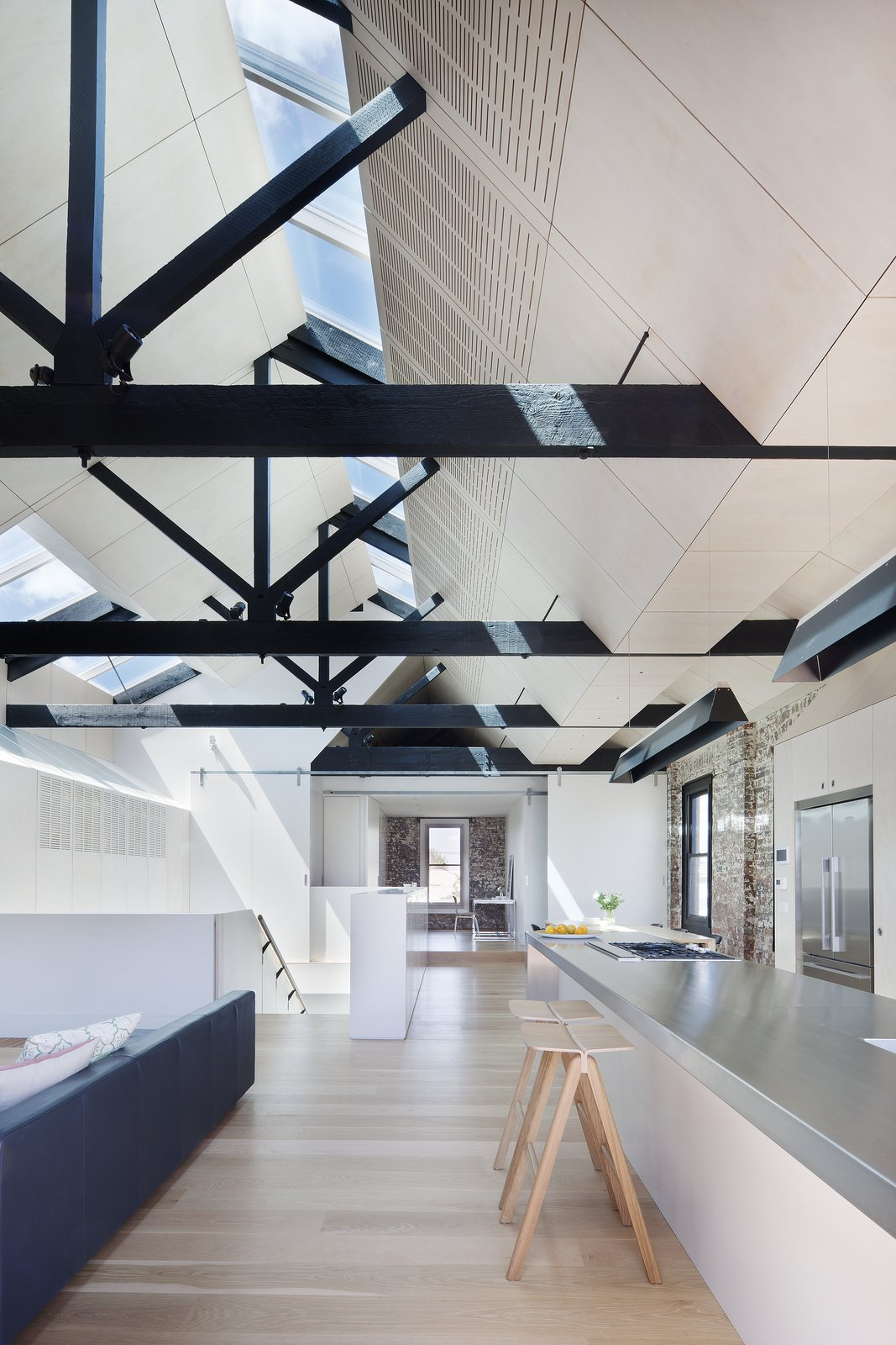 """The fact that the external walls were built to the site's boundary led to the solution of skylights as the one of the few means of introducing north light and good cross ventilation into the building,"" Simpson continues. The hanging lights are from Artemide while the hotplates and cooktops are from Barazza.  Water Factory by Kelly Dawson"