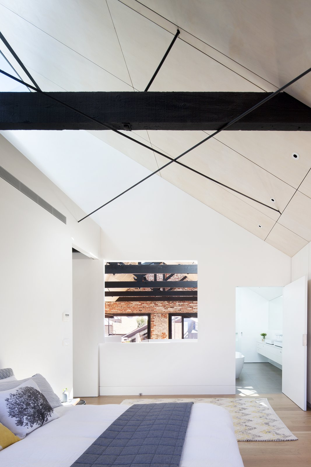 """Simpson wanted the design to capitalize on the original floor plan's abundance of space, but he also hoped to bolster intimacy by making rooms feel fluid. """"The master bedroom [opens] at its corner to become a viewing balcony to the 'central void.'""""  Bedrooms by Dwell from Water Factory"""