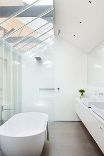 """""""A critical aspect of the project was the incorporation of natural light and ventilation within a broad footprint,"""" Simpson says. Conventionally private areas, like bedrooms and bathrooms, are therefore reinterpreted with more openness in mind. For instance, this bathroom's skylights mirror those found throughout the rest of the property. The bathtub, basins, and showerhead were all purchased at the Australian retailer Reece."""