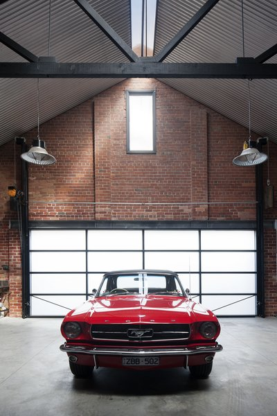 "The owners are car collectors, especially of ""vintage American Mustangs,"" Simpson says, so a nearly 23-foot-wide garage door opening was created at the rear of the building to access a space made for six prized rides."