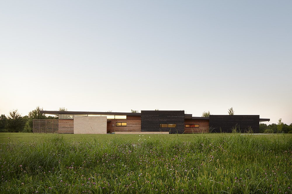 """Cedar rainscreen in a range of widths and color stains makes up the facade. The low-slung exterior was designed to respond to the surrounding topography. """"The design of the house provides a subtle, and at times, dramatic response to the open Midwestern terrain and offers a contemporary interpretation of 'prairie style' architecture,"""" El Dorado Inc principal Josh Shelton says.  Superb Single-Story Homes by Luke Hopping"""