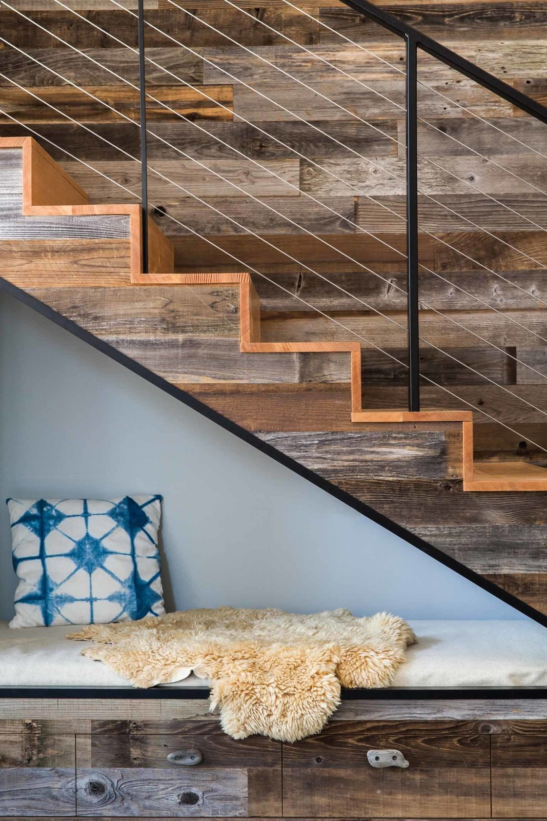 Staircase, Wood Tread, and Metal Railing A cozy reading nook fits underneath the stairs, saving floor space in the 1690-square-foot home.  Stairs from Don't Let Its Rustic Charm Fool You, This Net-Zero Home Plays for Team Modern