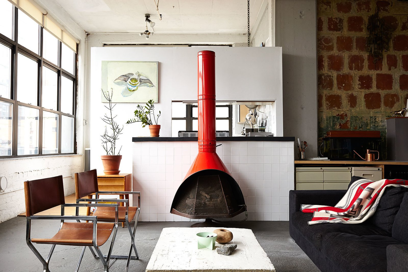 """""""I'm not trying to hide anything. I wanted to stay true to the industrial look,"""" explains Owen Wright, the owner of this Brooklyn loft. Owen works with his building's landlord and consequently has accrued countless pieces of furniture from both former tenants and Craigslist—including this 1960's fireplace and pair of steel frame chairs Owen had reupholstered. A BoConcept sofa and coffee table Owen constructed himself complete the living room.  97+ Modern Fireplace Ideas from One Person's Trash: This Brooklynite Built an Impressive Furniture Collection from Abandoned Items"""