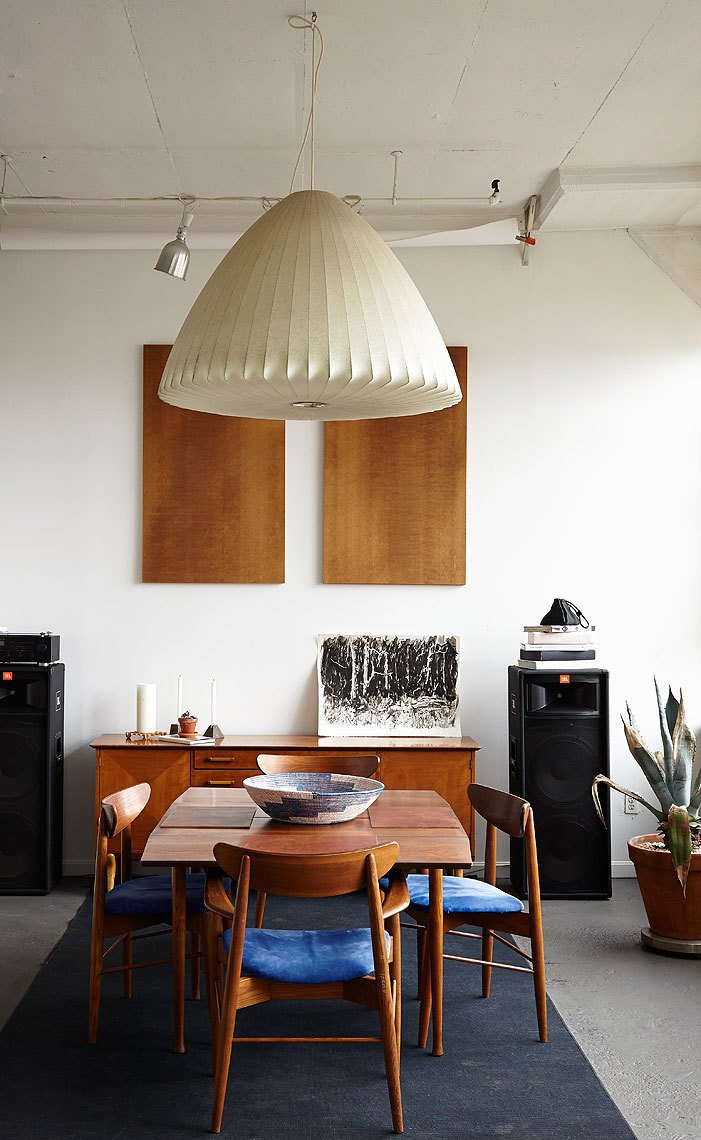 One of Owen's many hobbies is watercolor painting; the black and white painting seen here is one of his own. It sits just below a pair of decorative wall-hung particle boards. The credenza is a 1950s Renzo Rutili design for Johnson Furniture; the hanging lamp is by George Nelson. The dining room table and chairs are Danish-made midcentury teak models.  Rooms from One Person's Trash: This Brooklynite Built an Impressive Furniture Collection from Abandoned Items