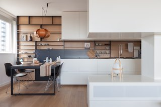 In Barcelona's Diagonal Mar district, architects Tobias Laarmann and Yolanda Yuste Lopex of YLAB Arquitectos renovated an automated studio apartment, with an eye towards carving out distinct stations throughout the open-plan space. Elongated countertops and cabinetry in the kitchen align with a large street-facing window to allow for maximum light and views, while also partitioning the apartment's communal areas. Rich oak wood lines the floors and the backsplash, recessed in the graphite shelving unit, and a quartet of Eames plastic shell chairs furnish the dining area.
