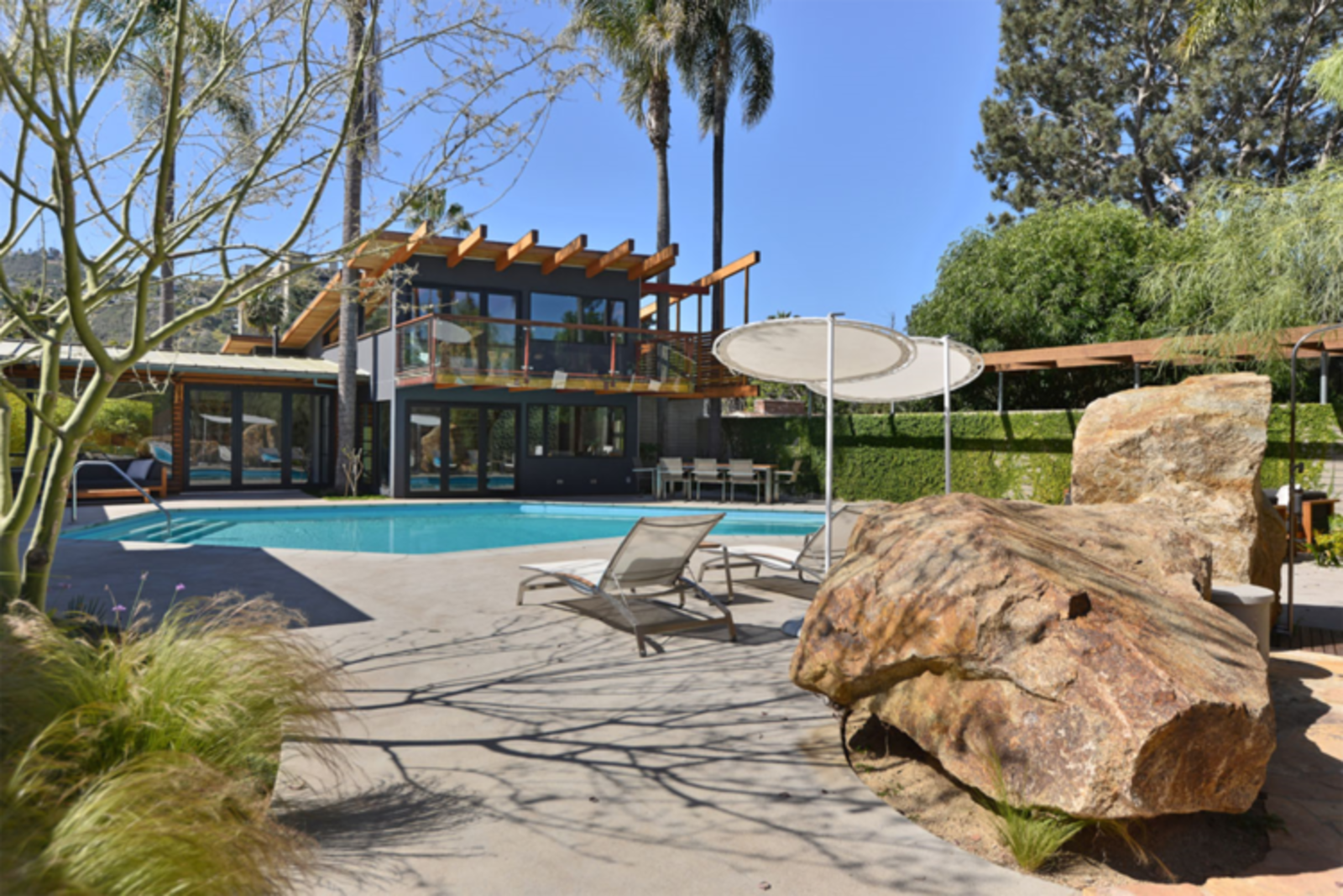 The entire backyard area is devised for enjoying the bright blue skies. To keep all the sections connected, he built a new one-and-a-half story unit that overlooks the pool and links to an additional garage loft.  Photo 4 of 12 in It's Time to Kick Off Dwell Home Tours—First Stop, San Diego