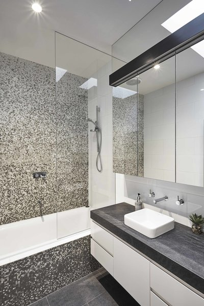 The new master bathroom features matte-black quartz countertops, a Cube sink, and a Scala wall-mount faucet. A Hansgrohe showerhead is surrounded by bold Gelsomino glass mosaic tile.