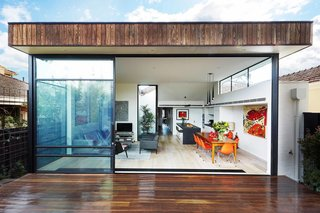 "The dramatic rear elevation showcases the open-plan living and dining room. Apart from the addition, the rest of the home maintained its ""traditional"" layout, with bedrooms branching off from a central hallway. Windows on all sides of the addition bring light in and make the space feel bright and expansive. Tonal and textural contrast can be seen between the burnt ash cladding at the exterior and the engineered European oak flooring at the interior. Through thoughtful design and space planning, the architects and owners made the biggest impact possible with only 500 square feet of added living space."