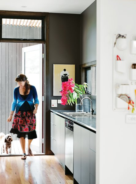 """Horne in the kitchen, where every element was part of the prebuilt package. Like elsewhere, the team placed a window over the door to bring in more light. """"The kitchen design continued the 'keep it simple' approach,"""" Horne says."""