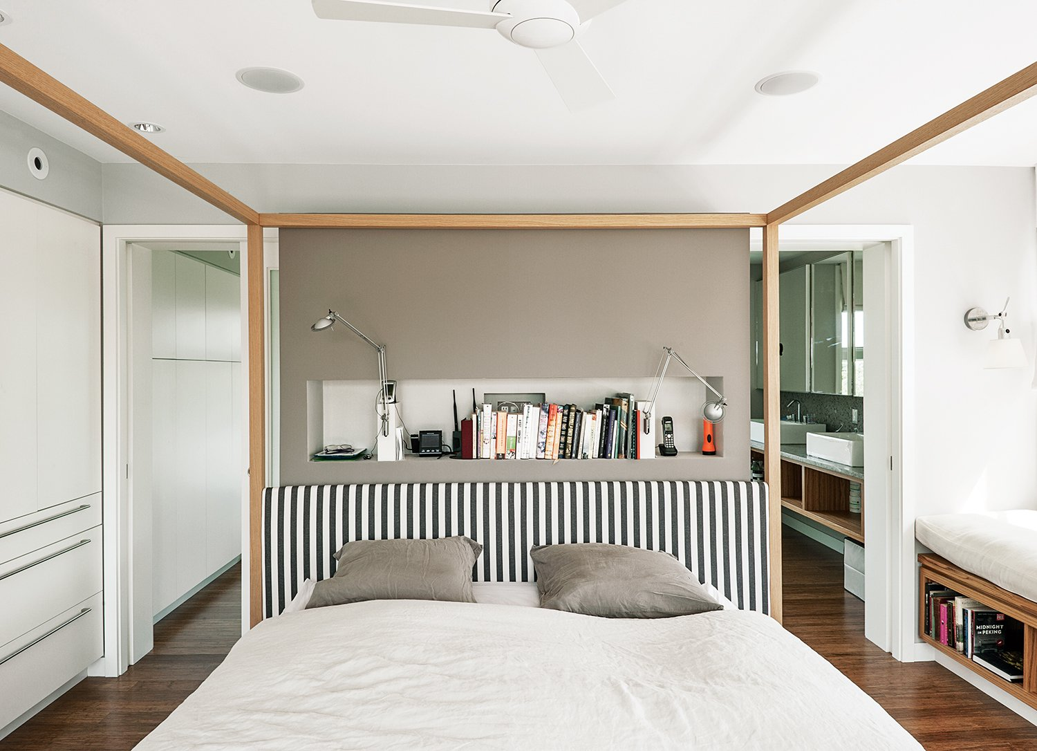 Bedroom, Bed, and Medium Hardwood Floor An Alcova bed from B&B Italia dominates the master bedroom. A niche behind the bed holds Berenice wall lamps by Luceplan, and the walls are painted in Cornforth White and Charleston Gray from Farrow & Ball.  Photo 8 of 11 in An Unconventional Prefab on Fishers Island