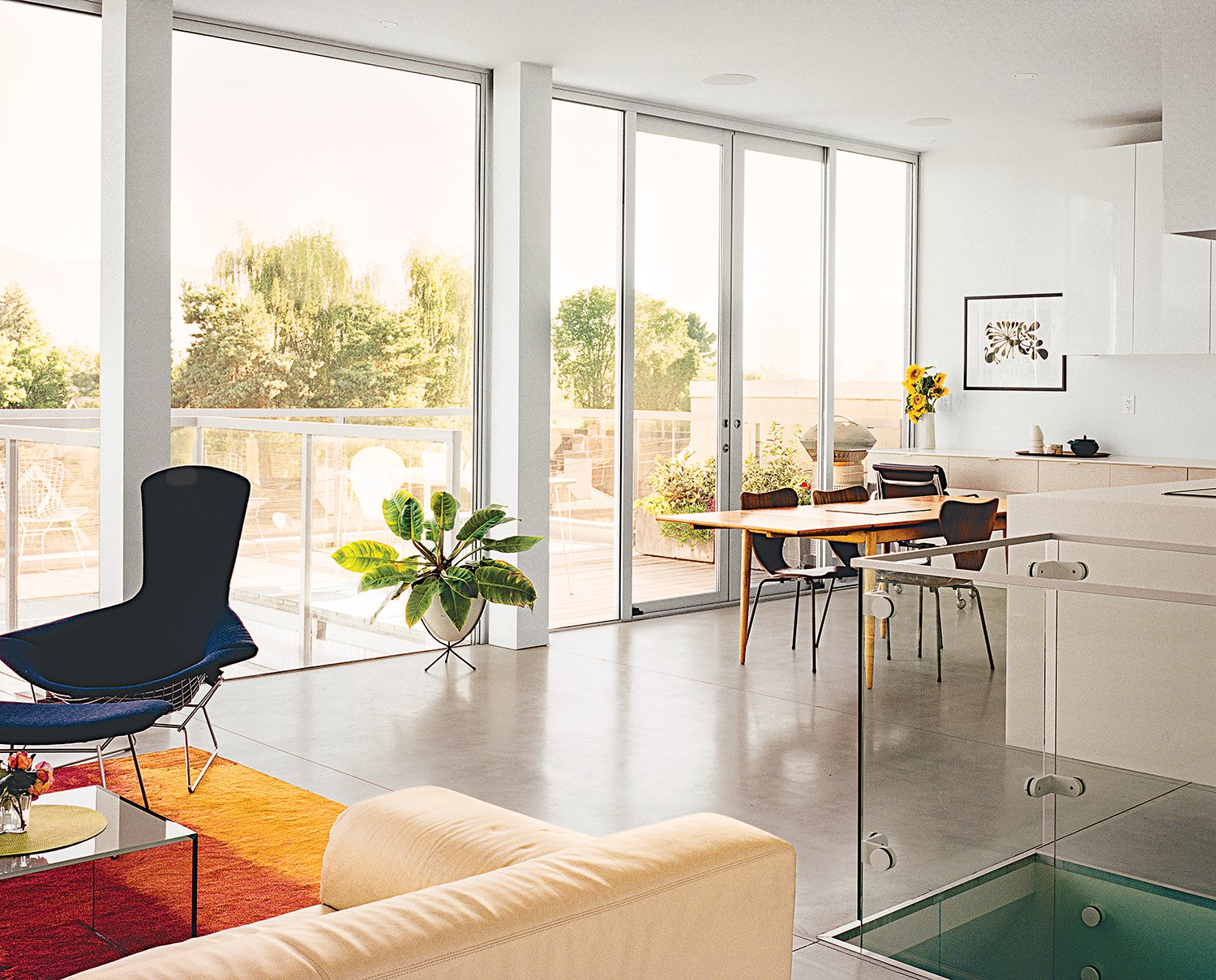 The living-dining area of their own residence is lined with doors and windows from Phoenix Glass for Columbia Aluminum Products.  Photo 1 of 7 in A Modern Multiunit Prefab Prototype in Vancouver