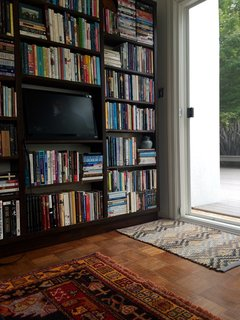 A large personal library, featuring patterned rugs, adds to the home's charm.
