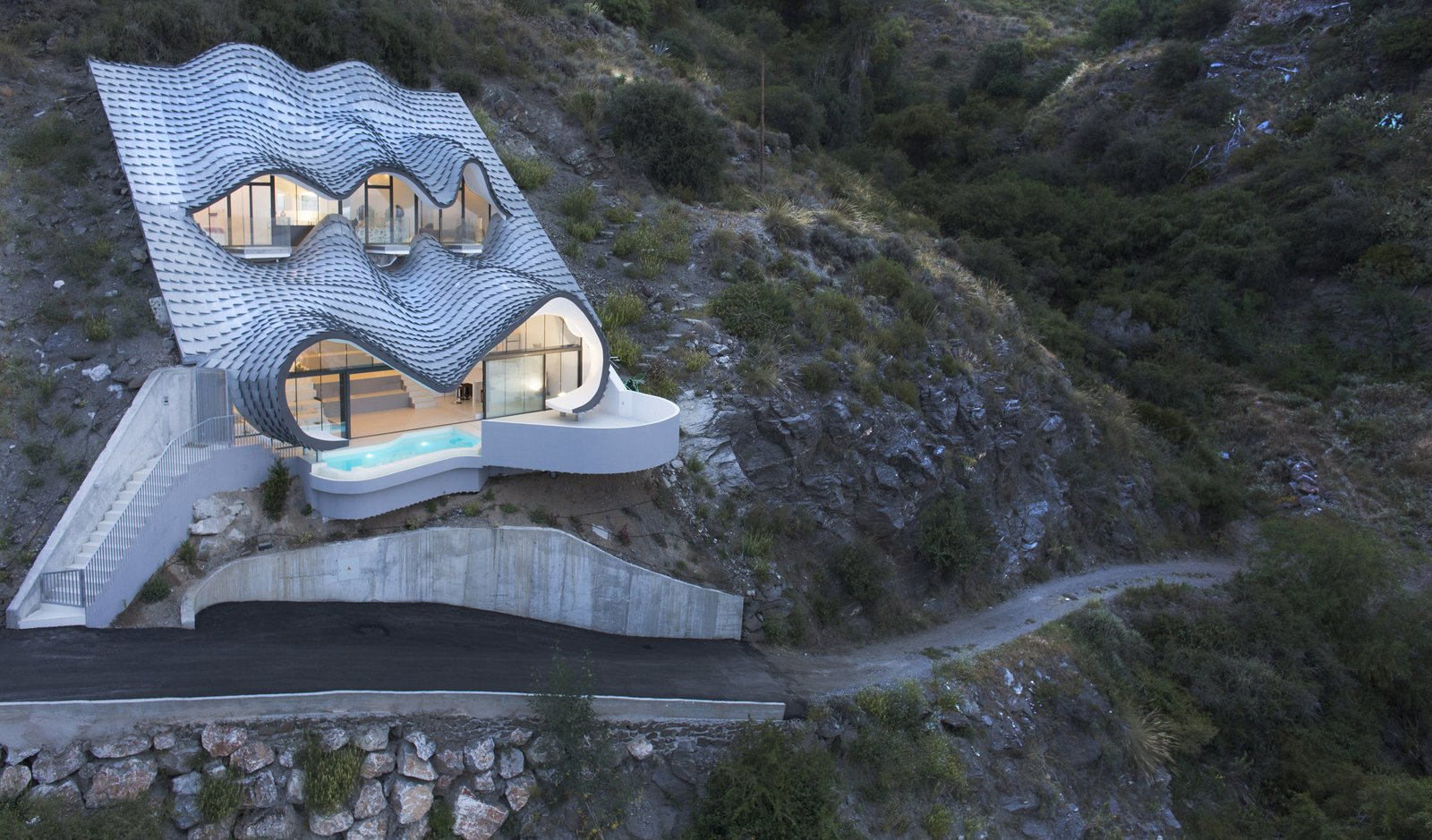 """Exterior, House Building Type, and Curved RoofLine GilBartolomé Architects says the metal facade looks like """"the skin of a dragon set in the ground when seen from below"""" but """"waves of the sea when seen from above.""""  Best Photos from Cliff House"""