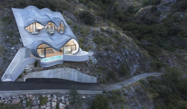 """GilBartolomé Architects says the metal facade looks like """"the skin of a dragon set in the ground when seen from below"""" but """"waves of the sea when seen from above."""""""