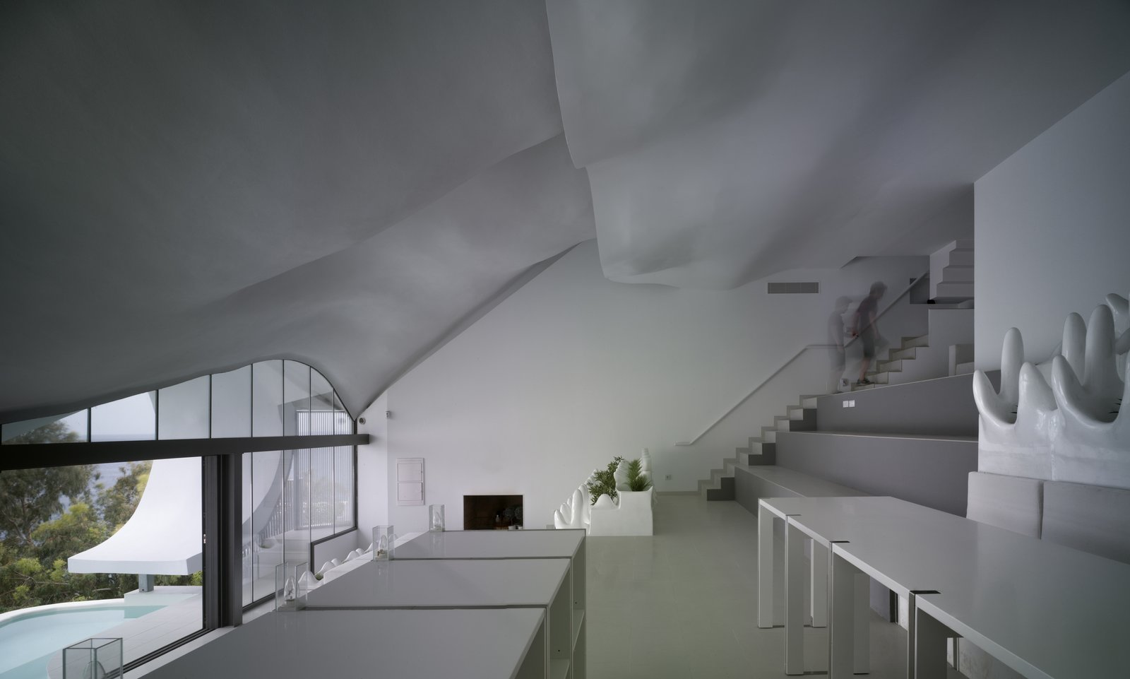 The reinforced concrete shell requires no columns, leaving the 47.5-foot-wide interior totally open. The living room doubles as a stage and the terraced seating can accommodate 70. A large sliding glass door separates the living room from the pool just outside.  Cliff House by Zachary Edelson