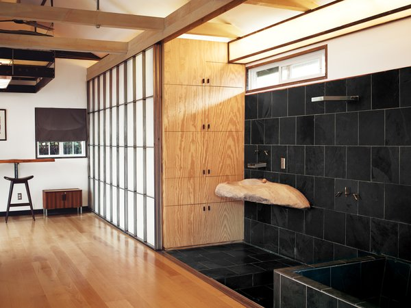Custom shoji-inspired screens of Roberts's design conceal the closet and extend to provide privacy for the adjacent shower and soaking tub.