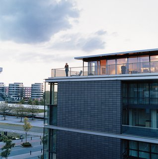 Cox enjoys the view from his penthouse terrace. The steel used for the terrace, and the brick-colored cladding of the building, echo the industrial architecture of the area. The angles suggest a ship, a nautical link with Duisburg's past as a major port.