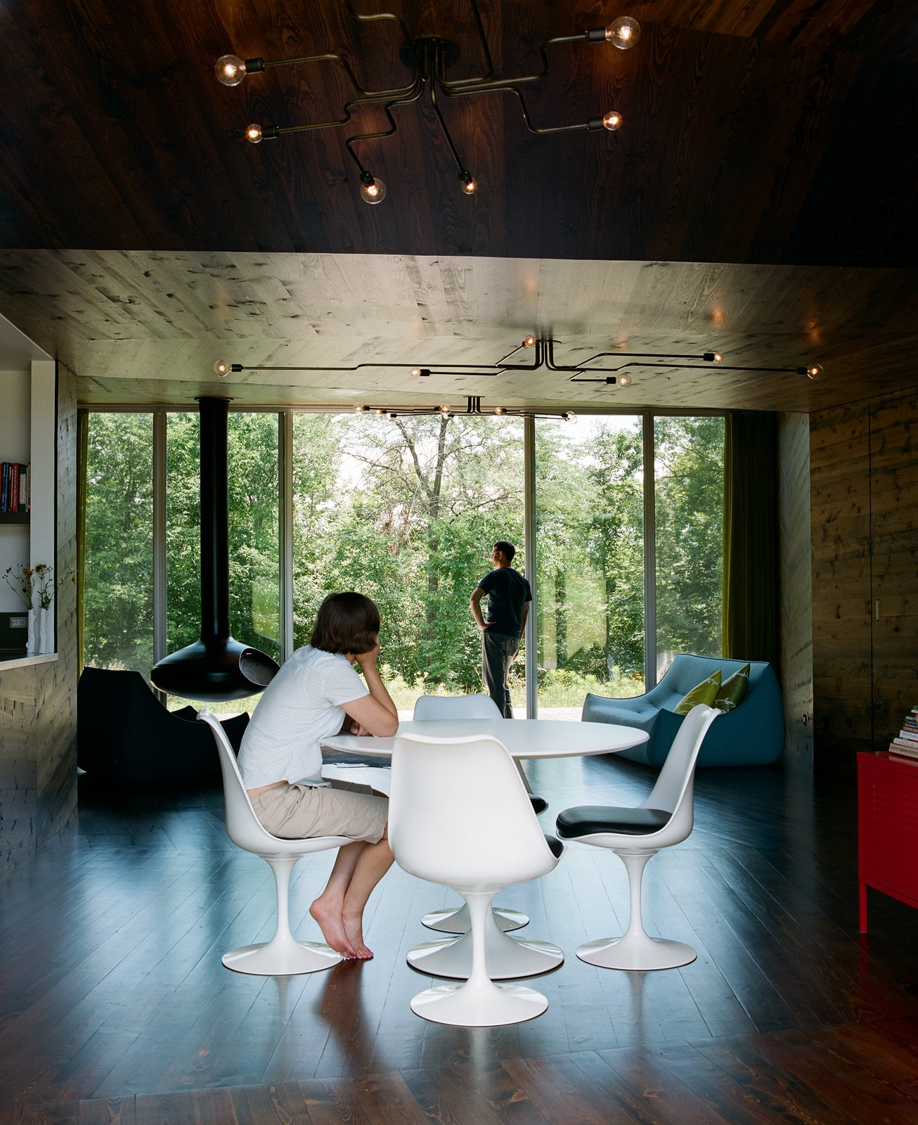 Dining Room, Chair, and Table In the main room, a Saarinen dining table is surrounded by four Tulip chairs, positioned to provide a mealtime panorama of the woods beyond the house.  New Grass Roots by Dwell from Dining Room Design Ideas
