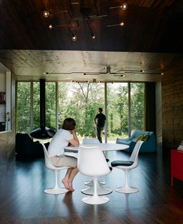 In the main room, a Saarinen dining table is surrounded by four Tulip chairs, positioned to provide a mealtime panorama of the woods beyond the house.
