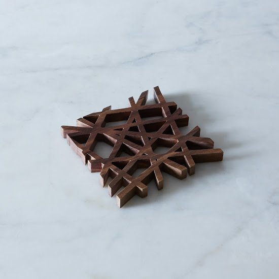 MID-CENTURY MODERN TRIVET $45 – $100  Designed by Fredrick Arndt in eco-friendly American black walnut, this trivet is right up our ally. We love the variation in the wood grain pattern and the sleek and structured design. It's a perfect bit of modernity for the table.  Mid Century from Holiday Gift Guide: For The Table