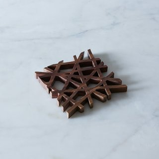 MID-CENTURY MODERN TRIVET $45 – $100  Designed by Fredrick Arndt in eco-friendly American black walnut, this trivet is right up our ally. We love the variation in the wood grain pattern and the sleek and structured design. It's a perfect bit of modernity for the table.