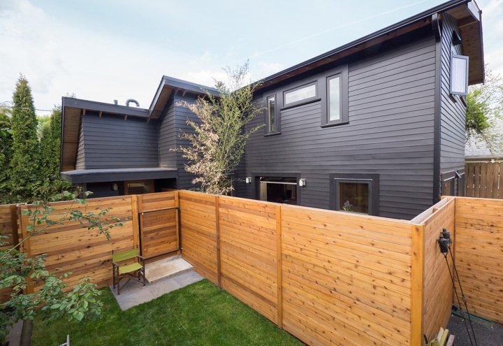 Outdoor, Wood Fences, Wall, Horizontal Fences, Wall, Grass, and Trees A client with grown children requested a small dwelling that could double as a work space. Cedar siding painted in Jet Black by Benjamin Moore contrasts the natural wood fencing.  30+ All-Black Exterior Modern Homes by Zachary Edelson from Best of #ModernMonday: The Changing Modern Home