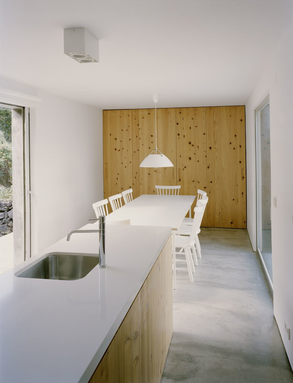 "The quiet, minimalist kitchen features a wall in the same ""criptoméria"" wood used for the bookshelf in the living room. A Davide Groppi Punto 2 PL light hangs over the dining table. Tagged: Kitchen, Concrete Floor, and Pendant Lighting.  This Modern Coastal Escape Sits Within 18th-Century Stone Walls by Patrick Sisson"