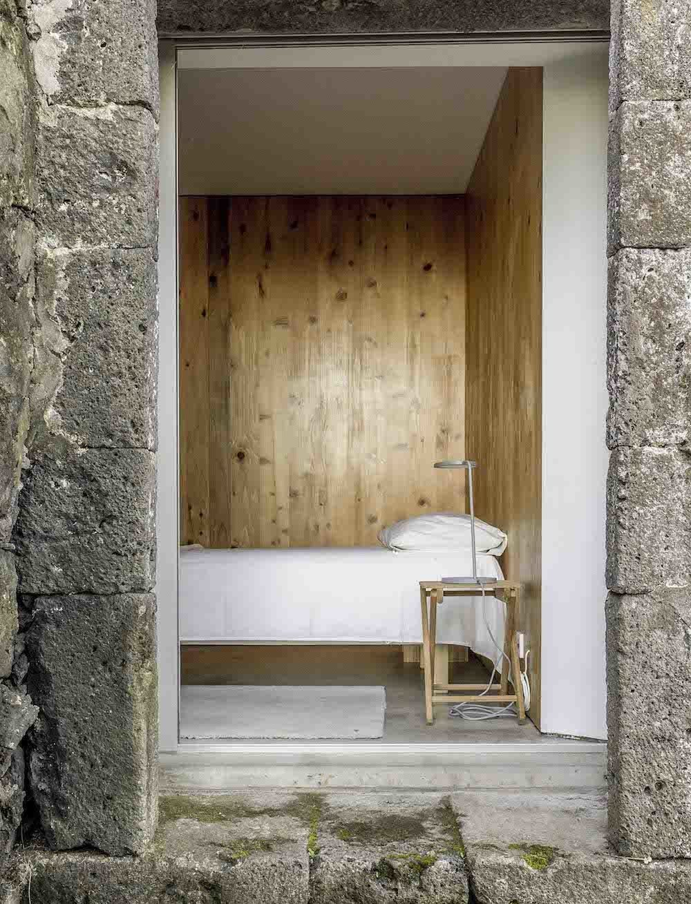 Bedroom and Bed Warm wooden walls ensure the simple bedroom setup, a low mattress next to a Muuto Leaf table lamp, offers more comfort than the cold stone exterior.  Best Photos from This Modern Coastal Escape Sits Within 18th-Century Stone Walls