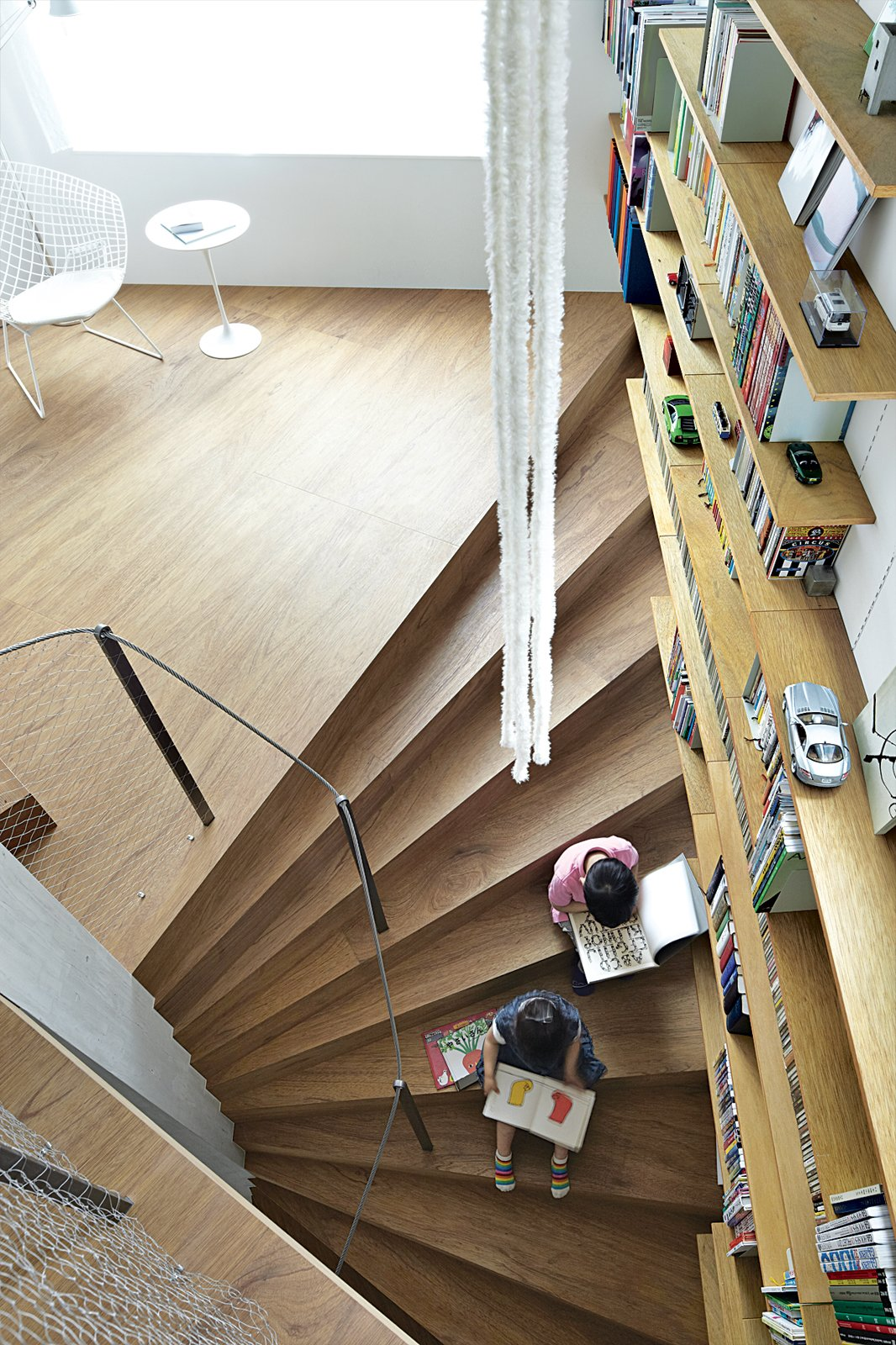 Staircase, Wood Tread, and Metal Railing Ran and her brother, Gen, read on one of the structure's 44 continuous steps.  Home Libraries that Take Book Storage to the Next Level by Diana Budds from This Sculptural Staircase Shapes an Entire Home