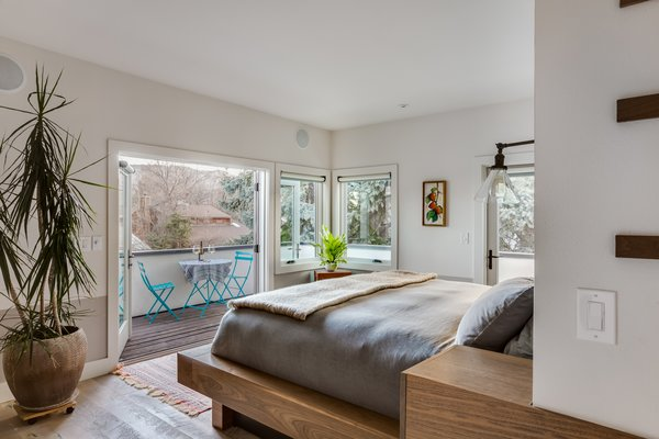 """The master suite is a large space anchored by a custom-built """"island"""" that holds the bed on one end and bathroom vanity on the other (see next slide).  """"Since we didn't want to push the whole house out to open up more space, I added a deck instead of altering the footprint,"""" says Juilland. The result, he says, is a cozy bedroom that doesn't feel confined."""