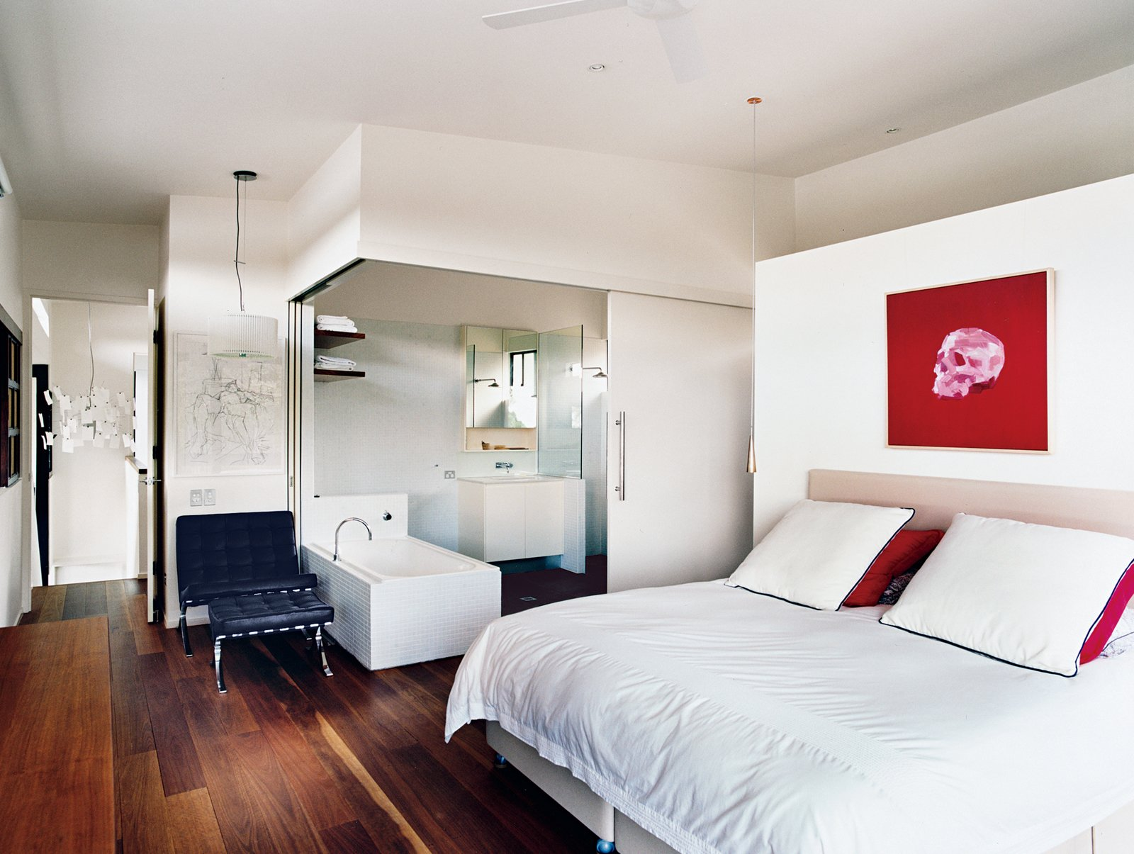 Bedroom, Bed, Chair, and Medium Hardwood Floor The serene all-white bathroom can be sealed off from the master bedroom by two sliding doors, or left open for a loftlike feel.  Photo 9 of 12 in Hillside Family Home in Australia
