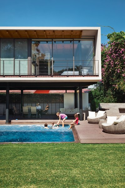 On an idyllic afternoon, members of the Oropeza and Castillo clans splash in the backyard pool framed by Trex decking and outfitted with furniture by Móbica.
