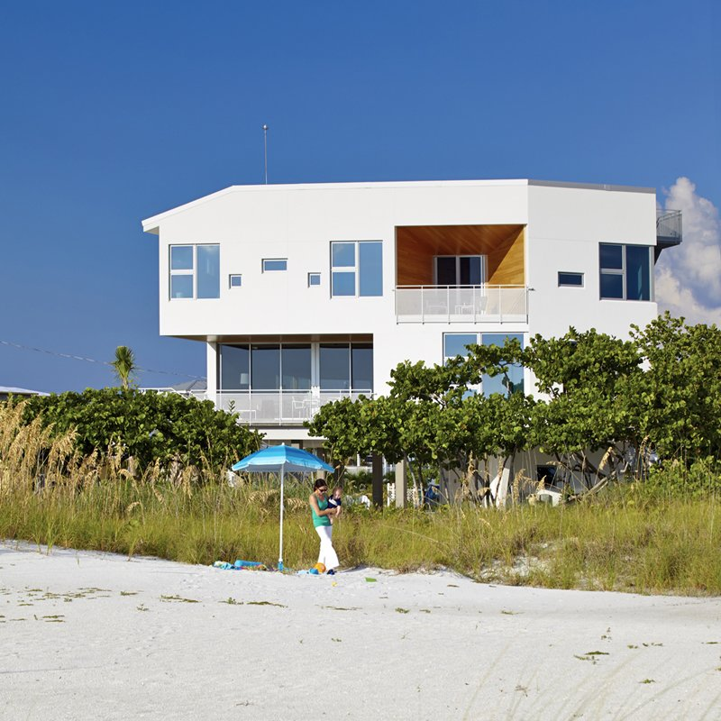 Architect Jody Beck with her son Jonah Tisdale, 1, in front of the family beach house she designed on Anna Maria Island, Florida. The home is essentially a bunker on the beach: its structure and envelope are constructed entirely of poured-in-place concrete to resist hurricane force winds while enabling dramatic cantilevers and unobstructed views of the Gulf of Mexico. Photo courtesy of Traction Architecture.  All-White Homes in Scorching Hot Climates by Luke Hopping from Angular Modern Beach House in Florida