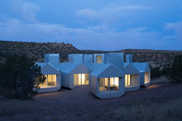 The Element House by MOS Architects stands on pylons, creating the illusion of it hovering over the desert floor. Nine thermal chimneys, one of which can be seen right, channel hot air out from the interior living areas.