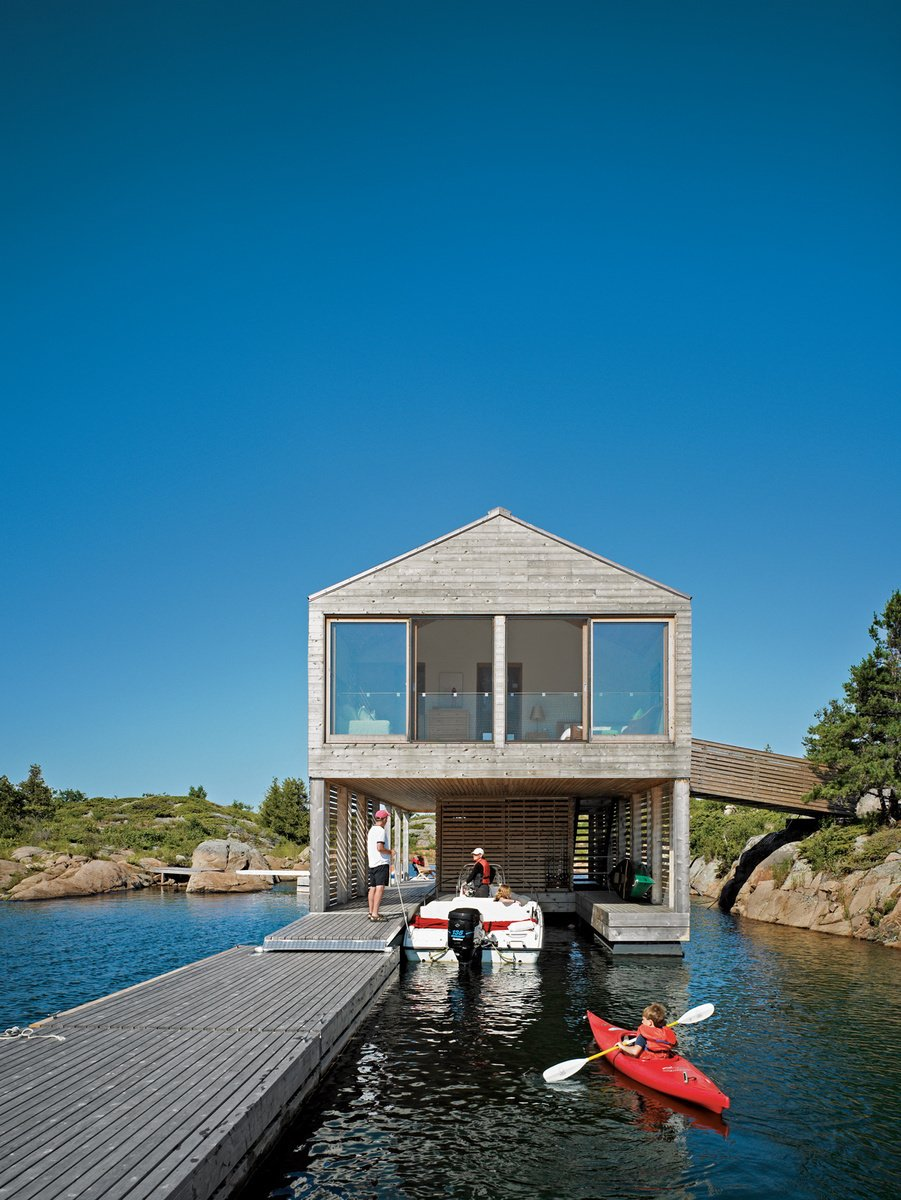 Exterior, House Building Type, Boathouse Building Type, and Wood Siding Material Cedar slats help this Ontario lake house float soundly atop still waters. Photo by: Raimund Koch  Best Photos from From Floating Homes to Prefab Moss-Covered Theaters, This Firm's Monograph Has It All
