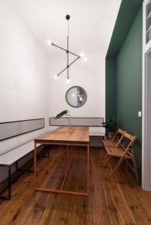 Two green accent walls—one seen here in the dining room—are the only departures from the strategically white backdrop. Wierciński and team designed the dining table and its orange steel frame, along with the seating benches and wall-mounted seat backs. A Sticks pendant light from Nowodvorski illuminates the space.